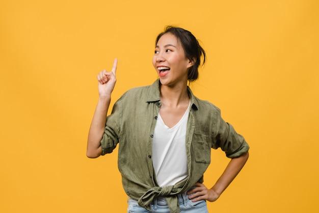 Portret młodej azjatyckiej damy uśmiechający się z radosnym wyrazem twarzy, pokazuje coś niesamowitego w pustej przestrzeni w swobodnym ubraniu i stojącej odizolowanej nad żółtą ścianą. koncepcja wyraz twarzy.