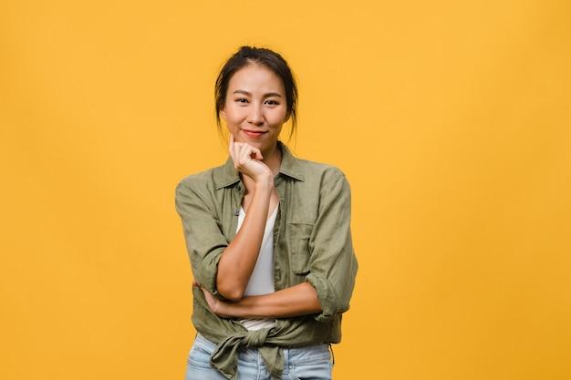 Portret młodej azjatyckiej damy z pozytywnym wyrazem twarzy, skrzyżowanymi rękami, szeroko uśmiechniętym, ubrana w luźne ubranie na żółtej ścianie. szczęśliwa urocza zadowolona kobieta raduje się sukcesem.