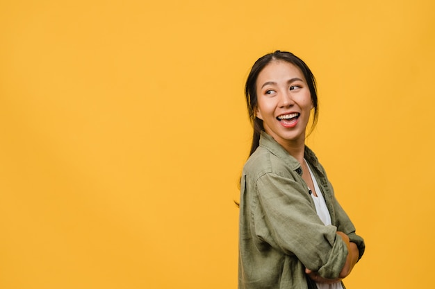 Portret młodej azjatyckiej damy z pozytywnym wyrazem twarzy, ze skrzyżowanymi ramionami, szeroko uśmiechnięty, ubrana w luźną tkaninę na żółtej ścianie. szczęśliwa urocza zadowolona kobieta raduje się sukcesem. koncepcja wyraz twarzy.