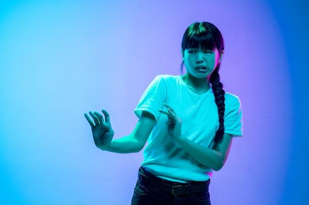Portret młodej azjatyckiej kobiety na gradientowym niebiesko-fioletowym tle studia w świetle neonowym