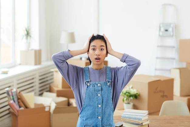 Portret młodej azjatyckiej kobiety panikującej w pasie, stojącej wśród kartonowych pudeł w pustym pokoju i patrząc wielkimi oczami, koncepcją przeprowadzki lub relokacji