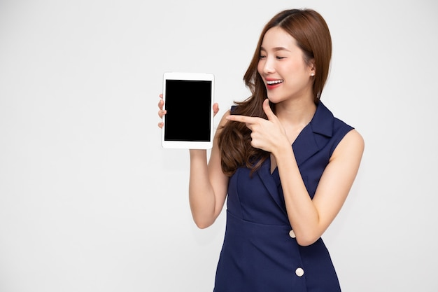 Portret młodej azjatyckiej kobiety pokazującej lub przedstawiającej aplikację tabletu pod ręką na białym tle na białym tle