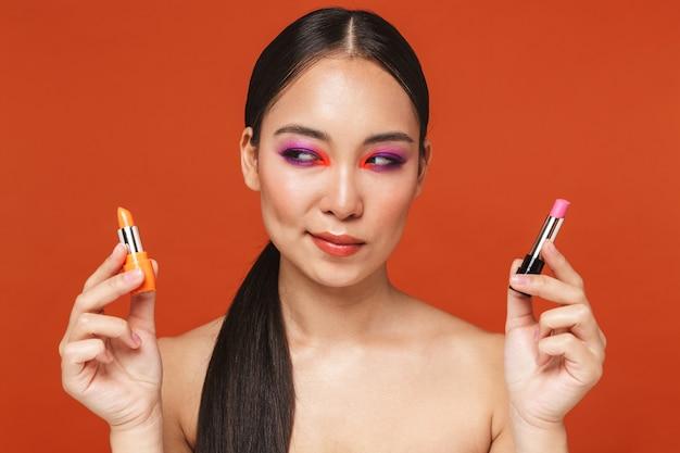 Portret młodej azjatyckiej kobiety topless z brunetką w jasnym makijażu, stojącej odizolowanej na czerwono, wybierającej spośród dwóch różnych szminek
