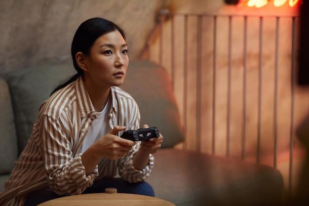 Portret młodej azjatyckiej kobiety trzymającej kontroler gamepada podczas grania w gry wideo za pośrednictwem konsoli do gier
