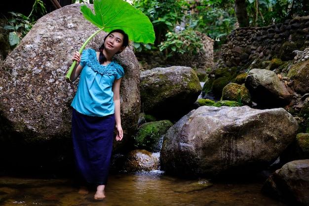 Portret młodej azjatyckiej kobiety trzymającej ogromny liść między skałami