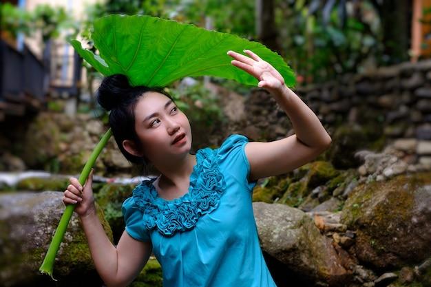 Portret młodej azjatyckiej kobiety trzymającej ogromny urlop