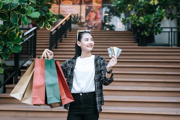 Portret młodej azjatyckiej kobiety w masce ochronnej, okulary na głowie stojącej z wielokolorową papierową torbą na zakupy