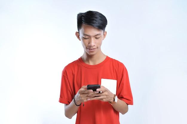 Portret młodej azjatyckiej studentki grającej na smartfonie na szarym tle
