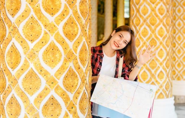 Portret młodej azjatyckiej turystki stojącej i trzymającej w ręku papierową mapę w pięknej tajskiej świątyni, uśmiecha się podczas machania ręką