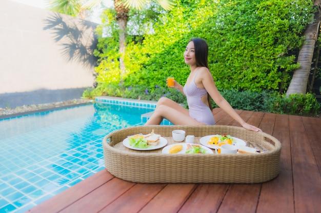 Portret młodej azjatykciej kobiety szczęśliwy uśmiech cieszy się z unosić się śniadaniową tacę w pływackim basenie w hotelu