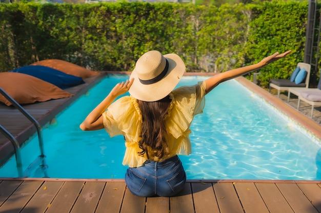 Portret młodej azjatykciej kobiety szczęśliwy uśmiech relaksuje wokoło plenerowego pływackiego basenu