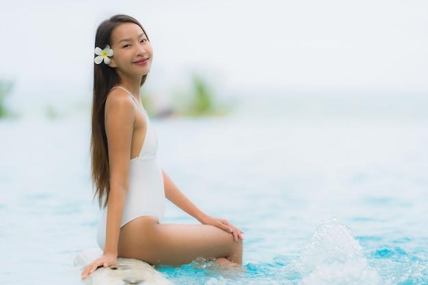 Portret młodej azjatykciej kobiety szczęśliwy uśmiech relaksuje wokoło pływackiego basenu w hotelowym kurorcie