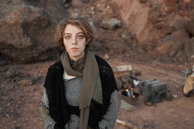 Portret młodej bezdomnej kobiety w podartych ubraniach, patrząc na kamerę, stojąc na zewnątrz
