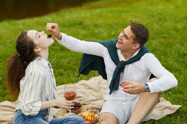 Portret młodej beztroskiej pary spędzającej romantyczną randkę na świeżym powietrzu, siedząc na zielonej trawie nad jeziorem i jedząc owoce