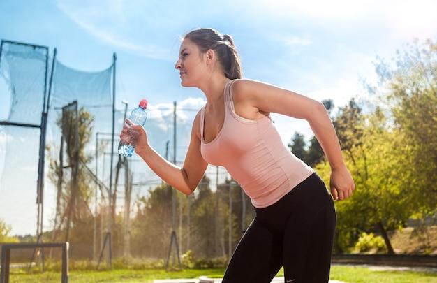 Portret młodej biegającej kobiety z butelką wody na stadionie