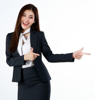 Portret młodej bizneswoman azjatyckiej w formalnym garniturze pozowanie i wskazujący palec na puste miejsce na prezent lub demonstrowanie towarów lub produktu w geście reklamowym, studio strzał na białym tle.