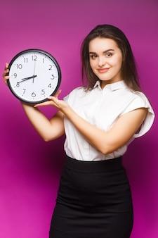 Portret młodej bizneswoman brunetka stojący na białym tle na fioletowy, pokazując zegar. skopiuj miejsce.