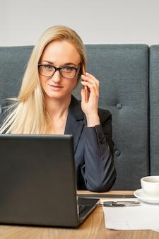 Portret młodej bizneswoman kaukaski w okularach wzywa smartfona z laptopem przy stoliku w kawiarni