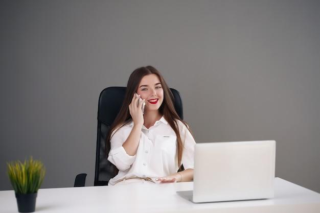 Portret młodej bizneswoman na sobie białą bluzkę siedzi w nowoczesnym biurze z laptopem i rozmawia przez telefon