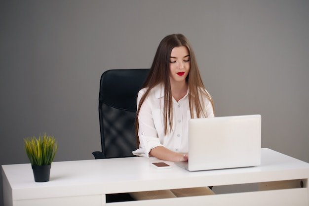 Portret młodej bizneswoman na sobie białą koszulę siedzi w nowoczesnym biurze z laptopem.