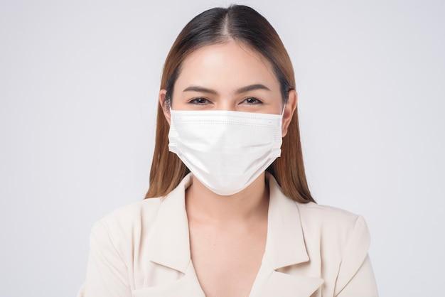 Portret młodej bizneswoman noszącej maskę chirurgiczną na białym tle studio