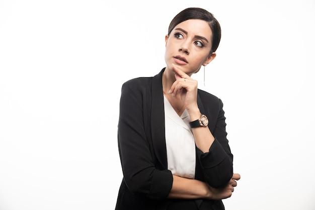 Portret młodej bizneswoman pozowanie na białej ścianie.