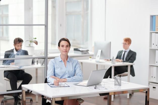 Portret młodej bizneswoman siedząc przy biurku w biurze z osobami pracującymi, kopia przestrzeń