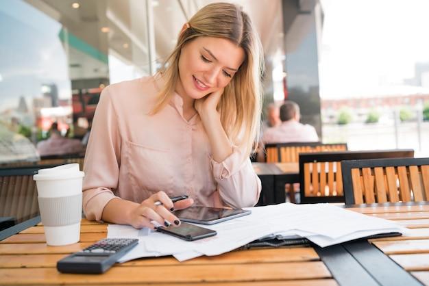 Portret młodej bizneswoman sprawdzanie dokumentacji i pracy w kawiarni