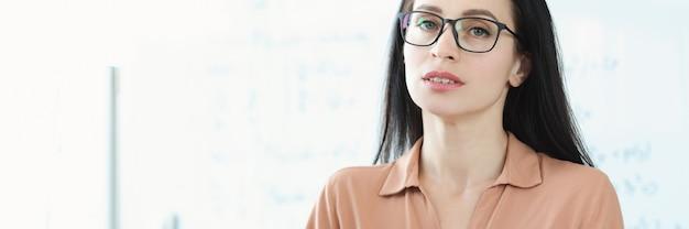 Portret młodej bizneswoman w okularach przy stole roboczym
