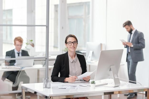 Portret młodej bizneswoman w okularach siedząc przy biurku w koncepcji biura, stażysty lub menedżera