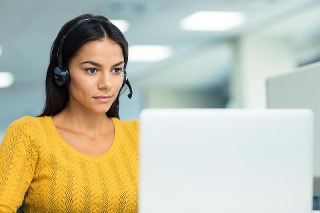 Portret młodej bizneswoman w słuchawkach przy użyciu laptopa w biurze