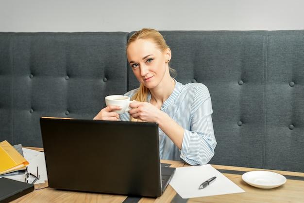 Portret młodej bizneswoman za pomocą laptopa siedząc przy stole przy filiżance kawy w kawiarni