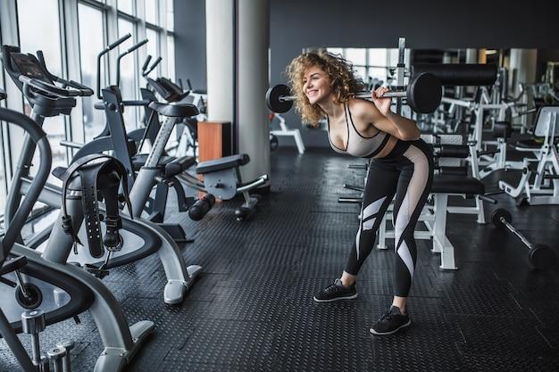 Portret młodej blond dziewczyny fitness robi przysiady ze sztangą na siłowni