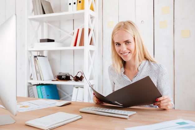 Portret młodej blond kobiety trzymającej otwarty folder w swoim miejscu pracy