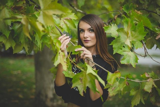 Portret młodej blondynki kobiety pozującej z liśćmi drzewa