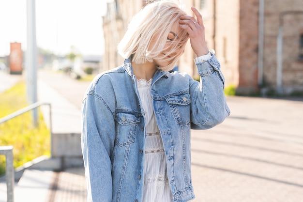 Portret młodej blondynki z rozczochranymi włosami na ulicy miasta