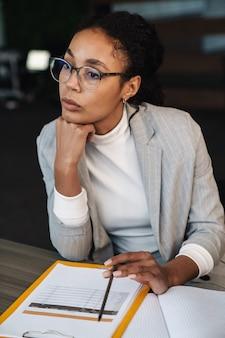 Portret młodej brunetki afroamerykańskiej bizneswoman siedzącej przy stole i pracującej z dokumentami w pokoju biurowym