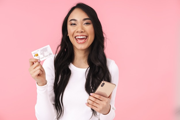 Portret młodej brunetki azjatyckiej kobiety z długimi włosami, trzymającej telefon i kartę kredytową na białym tle nad różową ścianą