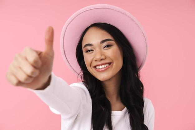 Portret młodej brunetki azjatykciej kobiety noszącej kapelusz uśmiechający się i pokazujący kciuk na białym tle nad różową ścianą