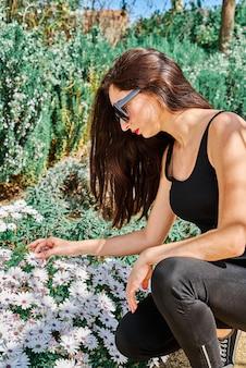 Portret młodej brunetki, długie włosy, okulary przeciwsłoneczne, z pomalowanymi ustami, w podkoszulku i czarnych dżinsach, zbieranie białych kwiatów w parku wiosną