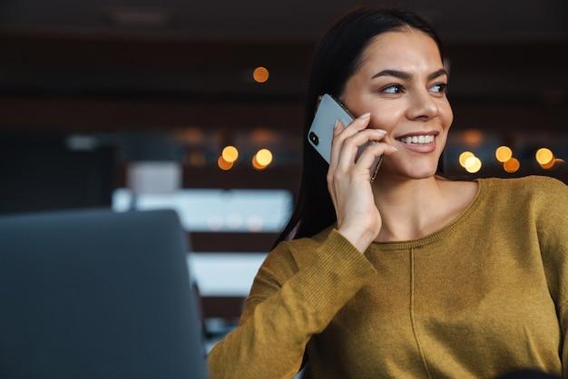 Portret młodej brunetki kaukaski bizneswoman rozmawia przez telefon komórkowy i korzysta z laptopa podczas pracy w biurze