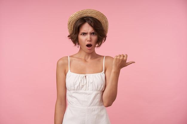 Portret młodej brunetki kobiety w białe lato, patrzącej ze zdezorientowaną twarzą, odsuwając kciuk na bok, stojąc, marszcząc brwi z otwartymi ustami