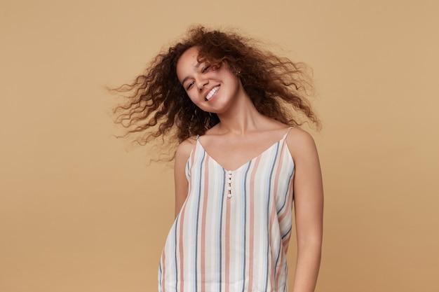 Portret młodej brunetki, machającej kręconymi włosami i uśmiechającej się wesoło, tańcząc na beżowym topie w letnie paski