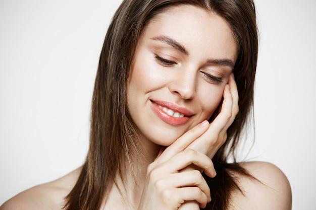 Portret młodej brunetki pięknej kobiety macania uśmiechnięta twarz. spa piękno koncepcji zdrowych i kosmetologii.