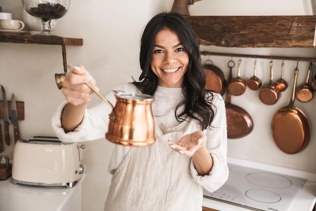 Portret młodej brunetki w wieku 30 lat w fartuchu stojącym z naczyniami w domu podczas gotowania w kuchni