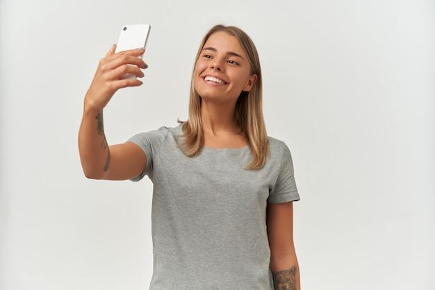 Portret młodej brunetki z idealnym uśmiechem, nosi szarą koszulkę, robiąc selfie na białym