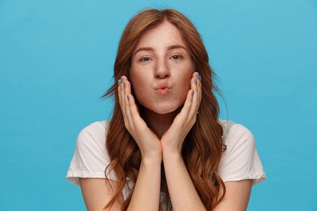 Portret młodej całkiem rudowłosej kobiety z lokami składającymi usta w pocałunek w powietrzu i trzymając ręce uniesione, patrząc na kamery, odizolowane na niebieskim tle