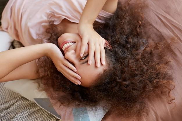 Portret młodej ciemnoskórej pani przeciw twarzy z rękami i leżąc na łóżku, ciesząc się słonecznym dniem w domu i uśmiechając się, spędza wolny dzień w domu.