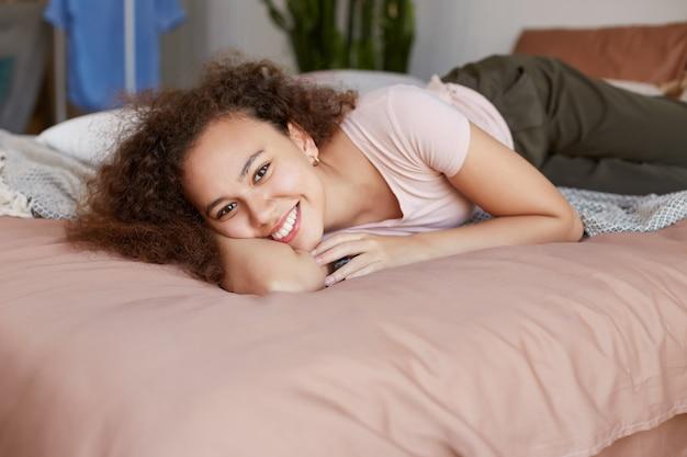 Portret młodej ciemnoskórej szczęśliwej damy leżącej na łóżku w swoim pokoju i uśmiechając się szeroko w słoneczny poranek w domu.