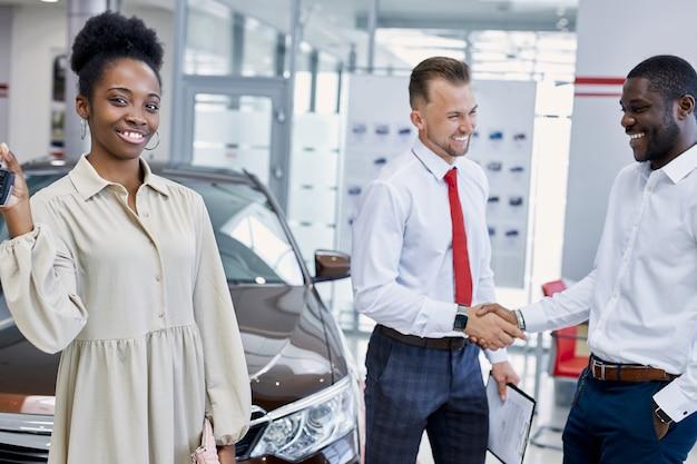 Portret młodej czarnej damy z kluczami do nowego samochodu w ręce